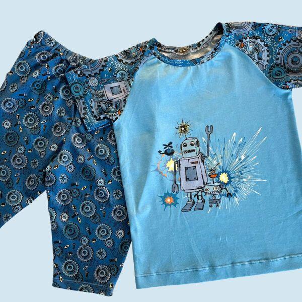 Tøj syet i bomuldsjersey med glade robotter og tandhjul blå baggrund